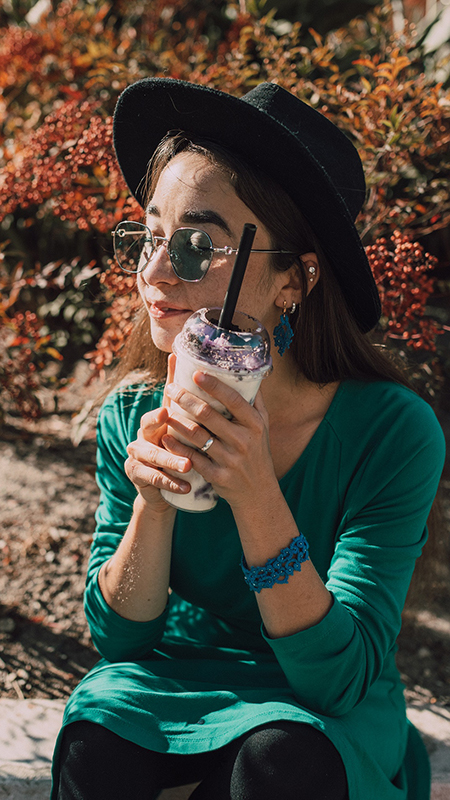 woman wearing a green shirt, a black hat, and sunglasses holding a boba tea drink up to her face